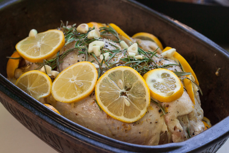Prepping the chicken with lemon and ginger before it makes its way into the oven.
